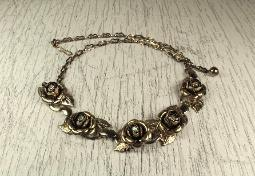 A shimmering light golden vintage choker, metal roses are centered with an opalescent aurora borealis stones